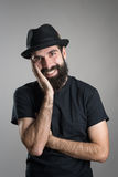 Friendly smiling bearded hipster wearing black t-shirt and hat with head resting on his hand Stock Images