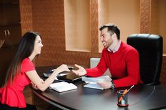 Friendly smiling businessman and businesswoman handshaking over the office desk after pleasant talk. stock image