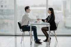 Friendly smiling businessman and businesswoman handshaking over the office desk after pleasant talk and effective negotiation, goo stock photography