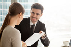 Friendly smiling businessman giving contract to businesswoman, o. Friendly smiling businessman giving official document to businesswoman, offering paper for royalty free stock photo