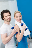 Friendly smiling couple working out with dumbbells Stock Images
