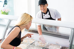 Friendly smiling deli worker helping a customer Stock Photography