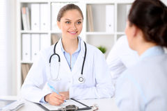 Friendly smiling doctor  and  patient sitting at the table. Very good news and high level medical service concept. Friendly smiling doctor and patient sitting Stock Images
