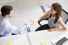 Friendly smiling employee shaking hand with young woman. Start work together, newly hired office worker meeting with female colleague, first day at work, good royalty free stock image