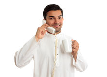 Friendly smiling ethnic businessman on telephone. A friendly smiling ethnic arab businessman on a telephone call.  He is holding a mug of coffee and is wearing Royalty Free Stock Image