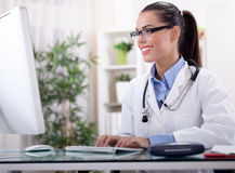 Friendly smiling female doctor the seal on prescription Stock Image