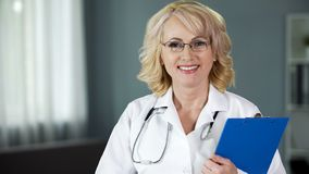 Friendly and smiling lady doctor looking into camera, giving hope for recovery royalty free stock images