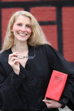 Friendly smiling lawyer with red law book under h Stock Photography