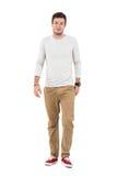 Friendly smiling man in beige pants walking towards camera Stock Image