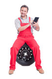 Friendly smiling mechanic using wireless tablet Royalty Free Stock Image