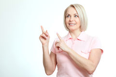 Friendly smiling middle-aged woman pointing at copyspace  on white background Royalty Free Stock Photography