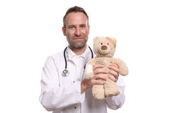 Friendly smiling paediatrician holding a teddy bear Stock Images
