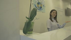 Friendly smiling receptionist in clinic showing the way stock footage