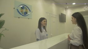 Friendly smiling receptionist greeting a young woman in clinic stock video