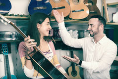 Friendly smiling  shopgirl helping male client to select guitar Royalty Free Stock Photo