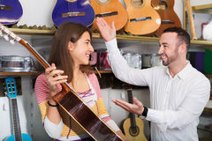 Friendly smiling  shopgirl helping male client to select guitar Royalty Free Stock Images