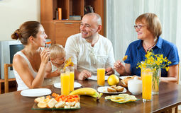 Friendly smiling three generations family eating fresh friuts Royalty Free Stock Photos