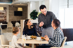 Friendly smiling waiter taking order at table of family having dinner together.  Stock Photography