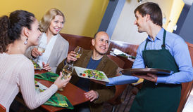 Friendly smiling waiter taking order at table of people. Having dinner together Royalty Free Stock Photography