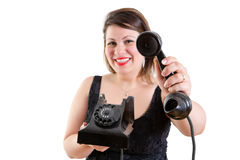 Friendly smiling woman holding out a telephone Stock Image