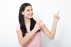 Friendly smiling woman pointing at copyspace isolated on white background Royalty Free Stock Image