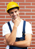 Friendly smiling worker in front of a brick wall Stock Photo