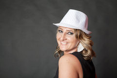 Friendly smiling young adult woman wearing white pinstripe hat Royalty Free Stock Photography