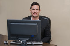 Friendly, smiling young businessman sitting at desk Royalty Free Stock Photo