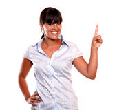 Friendly and smiling young female pointing up Stock Photo