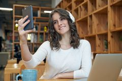 Friendly smiling young long-haired woman in a white jacket makes a selfie sitting at a table in a cafe with a laptop royalty free stock photo