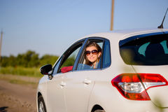 Friendly smiling young woman in a car Royalty Free Stock Images