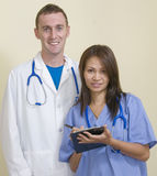 Friendly staff at hospital. Male doctor and Asian female nurse Royalty Free Stock Photo