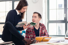 Friendly student helping his classmate by explaining and showing. Friendly student helping his classmate to understand new information by explaining and showing Royalty Free Stock Image