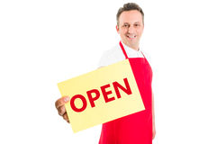Friendly supermarket employee holding open sign Stock Photos