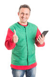 Friendly supermarket employee using wireless tablet. Supermarket employee using wireless tablet and showing thumb-up or like gesture Royalty Free Stock Images