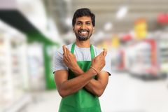 Supermarket worker making good luck gesture. Friendly supermarket or hypermarket indian employee making good luck gesture with crossed fingers and arms in store stock image