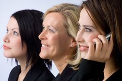 Friendly support. Three smiling businesswomen, one is having a phone call Royalty Free Stock Photos