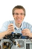 Friendly support technician. Studio shot of a young support technician with a trustworthy smile repairing a computer Stock Photo