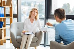 Friendly sympathetic doctor offering tissues. Do you need one. Friendly sympathetic female doctor looking at her patient and offering him paper tissues while Stock Photo