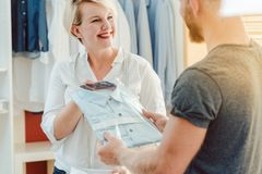 Tailor handing over finished bespoke shirt to customer. Friendly tailor handing over finished bespoke shirt to satisfied customer royalty free stock photos