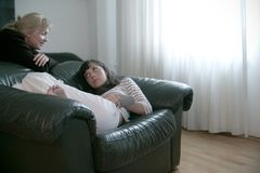 Friendly talk. One girl lying on a couch and talking to her friend or sister behind the couch Stock Images