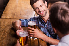 Friendly talk in bar. Top view of two happy young men talking to each other and gesturing while drinking beer at the bar counter Stock Photos