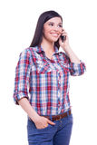 Friendly talk. Beautiful young woman talking on mobile phone and smiling while standing isolated on white Royalty Free Stock Photography