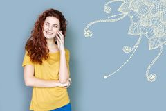 Emotional student smiling while having a friendly phone talk. Friendly talk. Cheerful young friendly student feeling happy while talking on the phone with her Royalty Free Stock Image