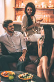Friendly talk. Cheerful young people enjoying food and drinks while spending nice time in cofortable chairs at home together Royalty Free Stock Photos