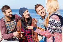Friendly talk. Four happy friends talking to each other and smiling while sitting on the beach and drinking beer Royalty Free Stock Image