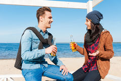 Friendly talk. Handsome young men and women talking to each other and smiling while drinking beer on the beach Royalty Free Stock Photography