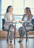 Friendly talk. Image of two friendly businesswomen talking by the cup of coffee in office Royalty Free Stock Image
