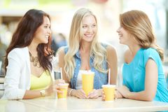 Friendly talk. Portrait of three happy girls chatting while having drink after shopping Royalty Free Stock Photography