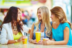 Friendly talk. Portrait of three happy girls chatting while having drink after shopping Stock Photo